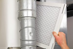 Male arm and hand replacing disposable air filter in residential air furnace.