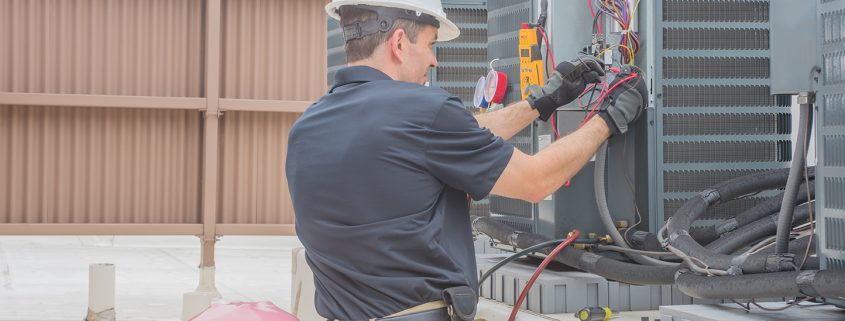 HVAC Tech Checking Condenser